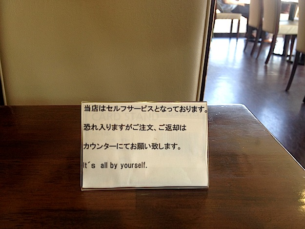 Meaning, please seat yourself. Or suit yourself and sit alone. You're on your own.