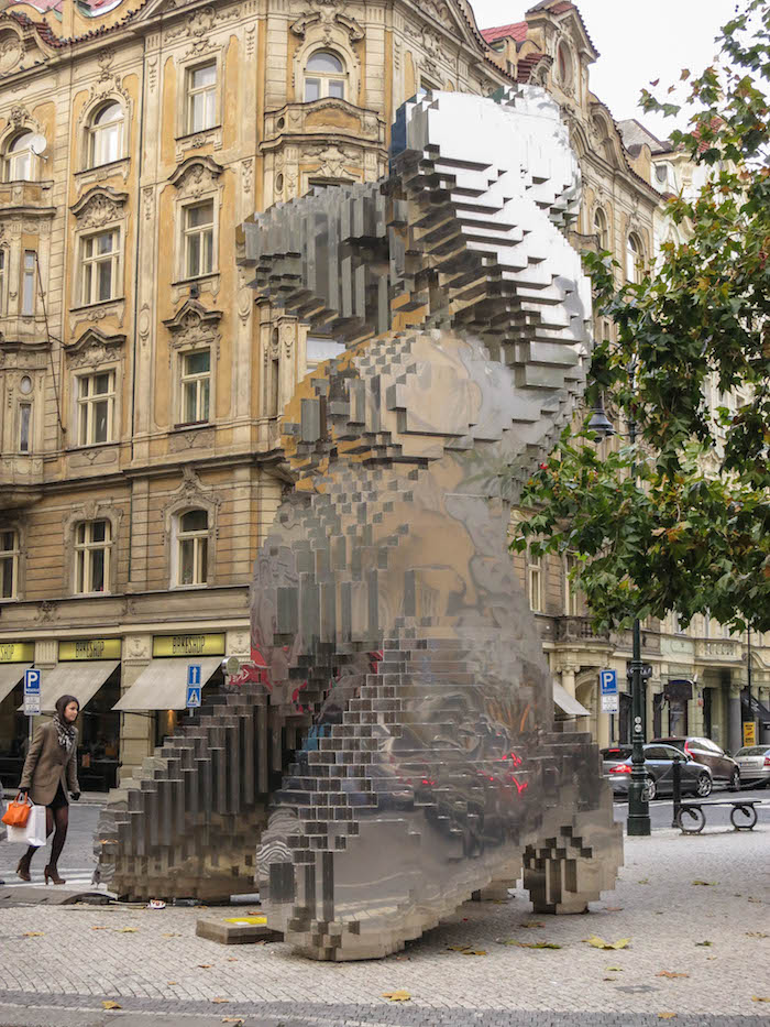 Modern sculpture amid historic buildings in central Prague